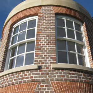 Curved white timber vertical sliding windows