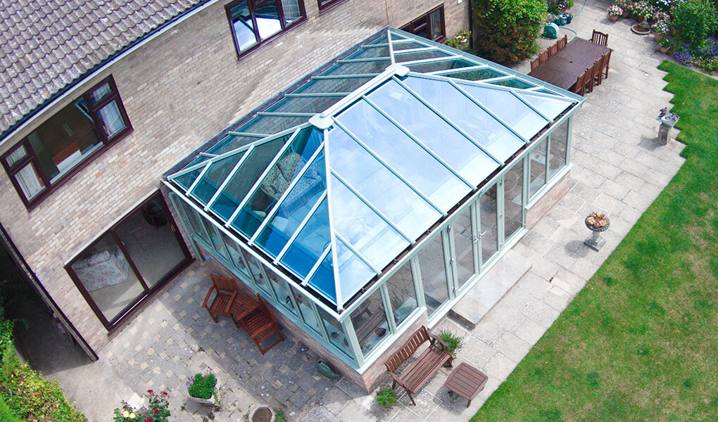 Sage green uPVC Edwardian conservatory with a glass roof