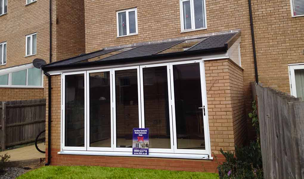 White upvc lean-to orangery leading out to a lawn