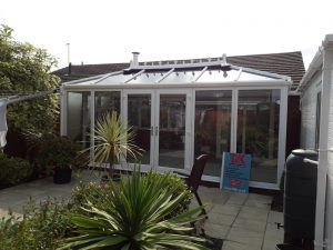 A traditional Edwardian conservatory in white in a back garden with palms in pots and a water butt on the right hand side.