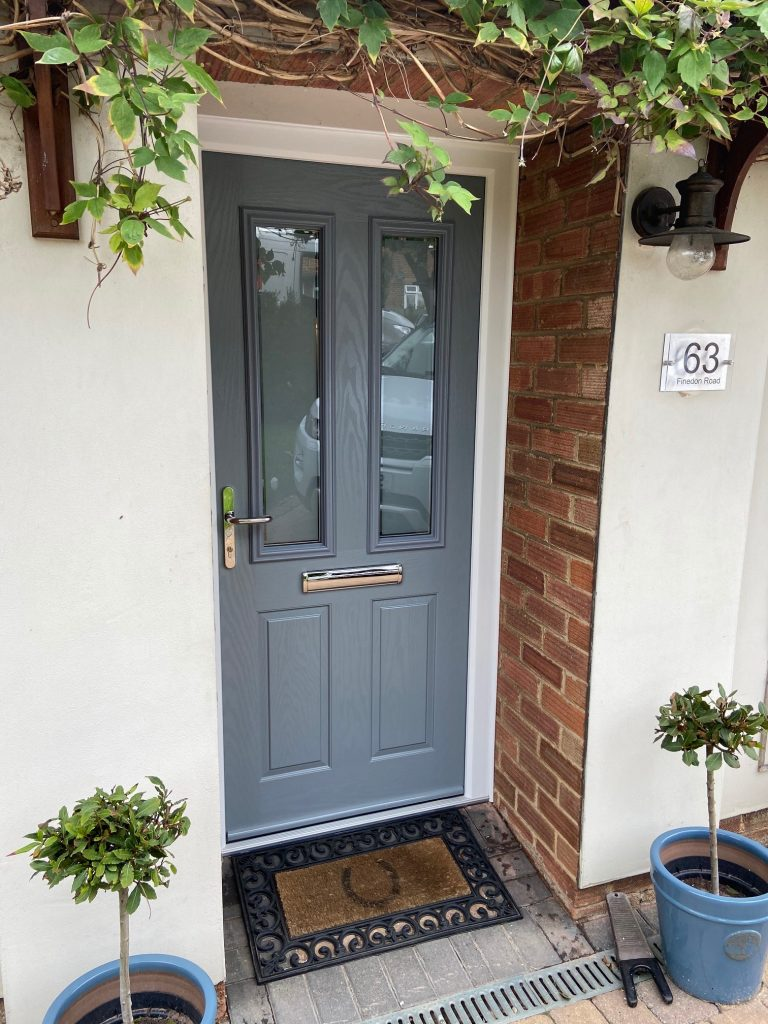 A Silver Grey Composite Door set in to a red brick wall with a horseshoe doormat and two pot plants outside.